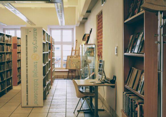 Wnętrze Wypożyczalni Literatury Pięknej i Obcojęzycznej - widok wnętrza od wejścia; regały z nowościami i literaturą obcojęzyczną, stanowisko komputerowe.